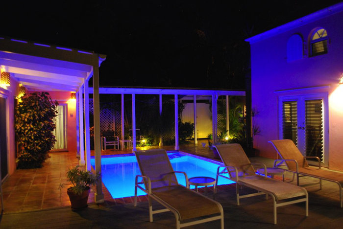 At night, the pool lights changing colors gently illuminate the courtyard